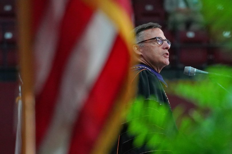 President Kevin O'Brien speaks at his inauguration. His face is framed by a flag and plant.