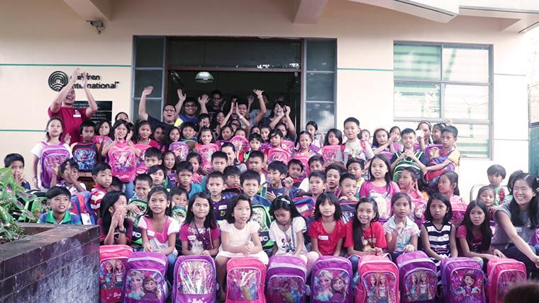 A group shot of students with their new backpacks.