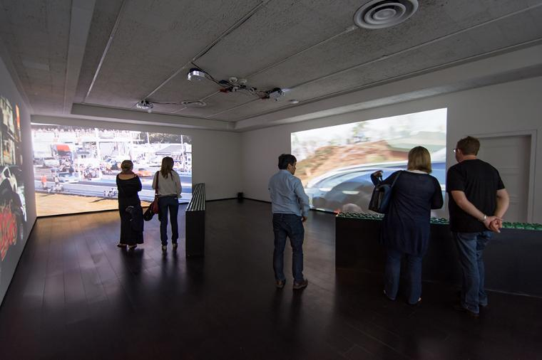 Visitors in a gallery watching video projections.
