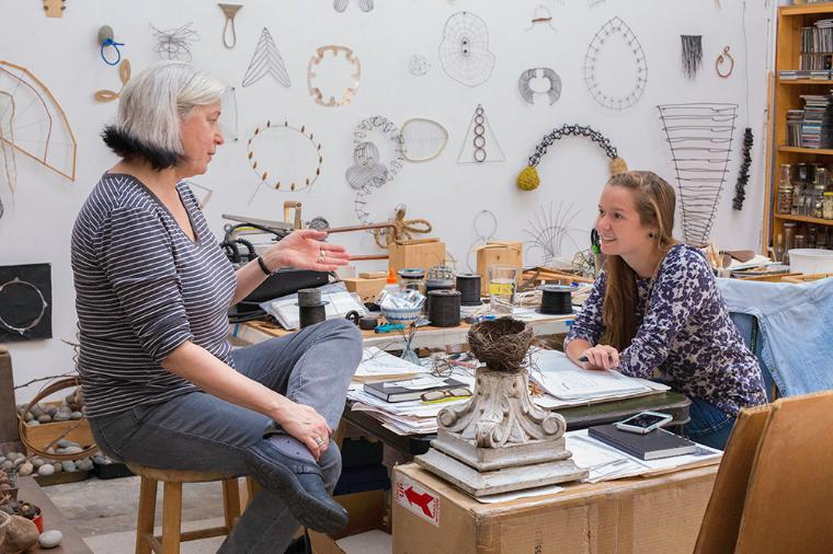 Student talking with artist Mari Andrews in her studio.