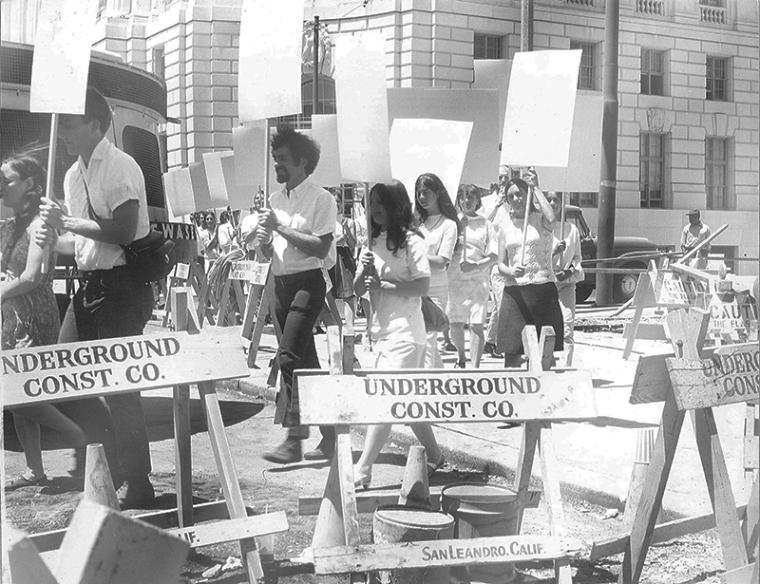 Black and white photograph of people marching in San Francisco with blank placard signs