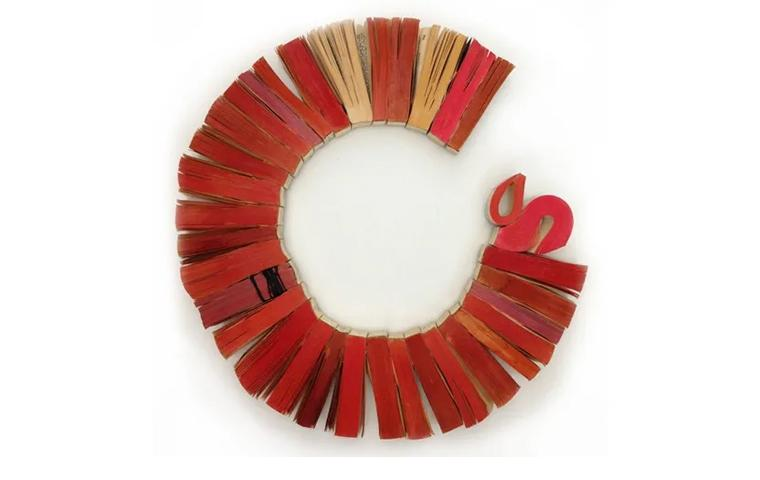Wall sculpture created from red book ends arranged in open circle
