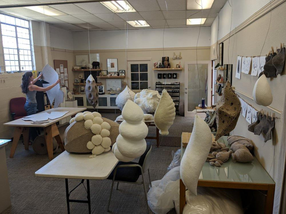 Artist Stephanie Metz stands in her studio examining a felt shape while the room is filled with felt and wool creations.