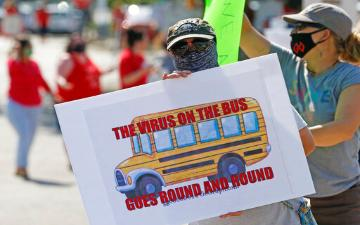a person wearing facemask and carrying a sign with an image of a school bus and slogal