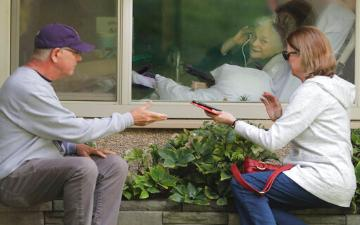A couple visit with elderly through window and phone to practice social distancing