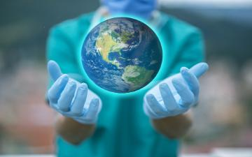 medical professional with outstretched hands holding a globe