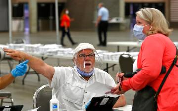 A poll worker wearing PPE directs a voter wearing a face mask to polling station