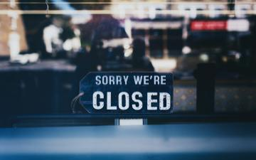 close-up of sorry we're closed sign on glass window