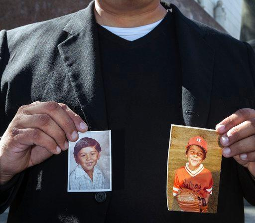 Michael Duran, a plaintiff in a sex abuse settlement with the Roman Catholic Archdiocese of Los Angeles, holds up pictures of himself when he was a child (AP Photo/Damian Dovarganes, file).