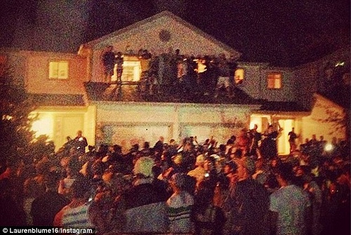 Large crowd gathered outside of a house at night image link to story