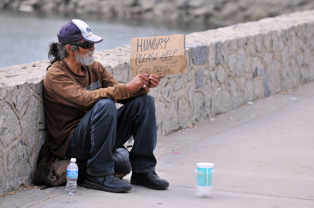 Homeless man holding sign that says