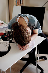 Young woman with her head down on her desk image link to story