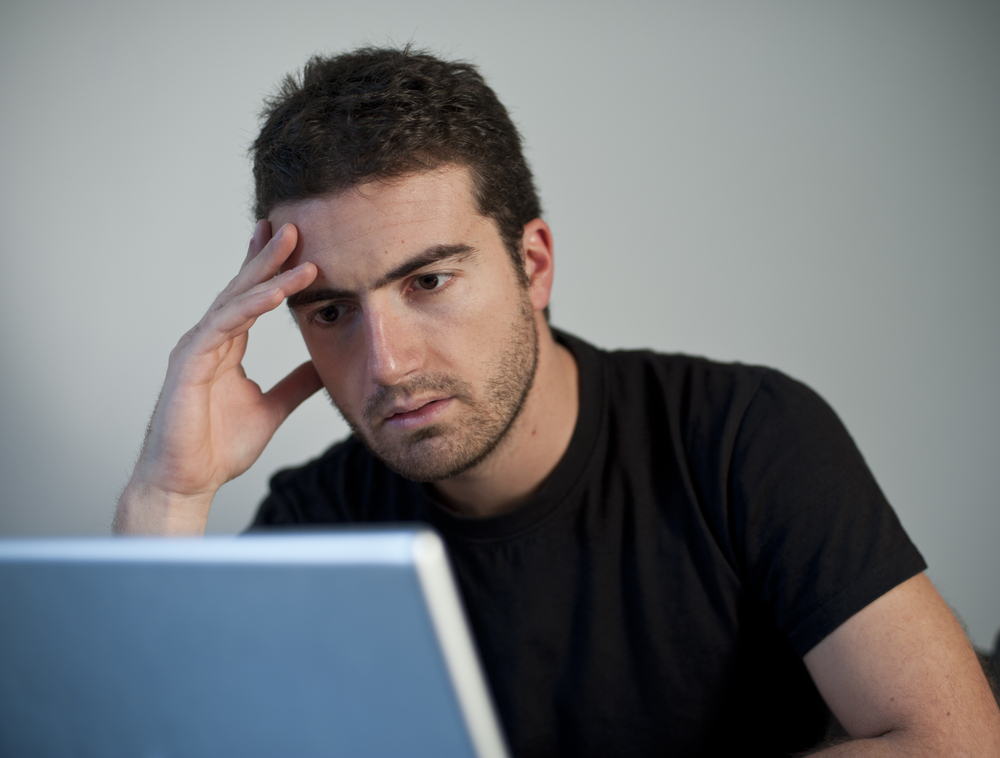 Man looking frustrated at the computer