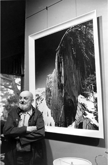 Ansel Adams standing in front of his photograph,