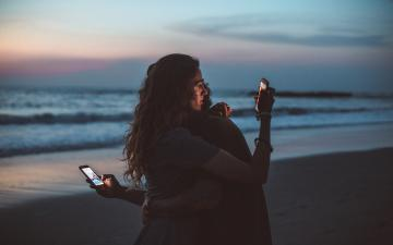 couple embracing on the beach, each looking at mobile device screens