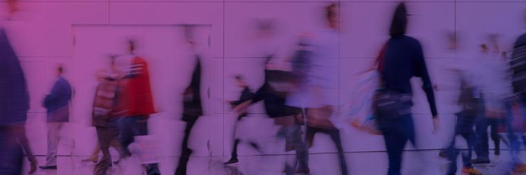 blurred abstract image of people walking in a building hallway