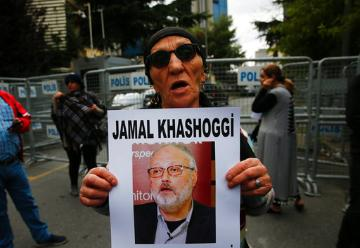 Activist holding poster with photo of missing Saudi journalist Jamal Khashoggi (AP Images/Lefteris Pitarakis).