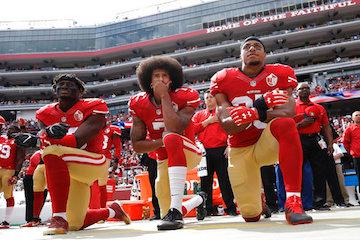 San Francisco 49ers outside linebacker Eli Harold, left, quarterback Colin Kaepernick, center, and safety Eric Reid kneel during the national anthem before the team's NFL football game against the Dallas Cowboys in Santa Clara, Calif. Kaepernick accepted Sports Illustrated's Muhammad Ali Legacy Award from Beyonce on Tuesday night, Dec. 5, 2017, and promised that