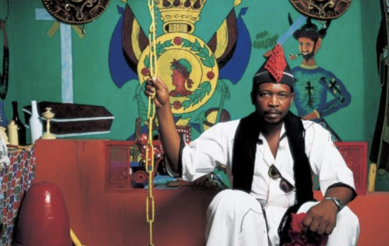 Photograph of vodou priest Volny Derosier, seated in his vodou temple in La Petite Rivière de l'Artibonite, Haiti. Photo courtesy of Haiti ©Phyllis Galembo. image link to story