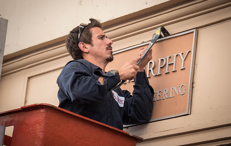 A University Operations employee removes a naming plaque on Bannan Hall during the move to Heafey Hall in December 2018. Photo by Charles Barry image link to story