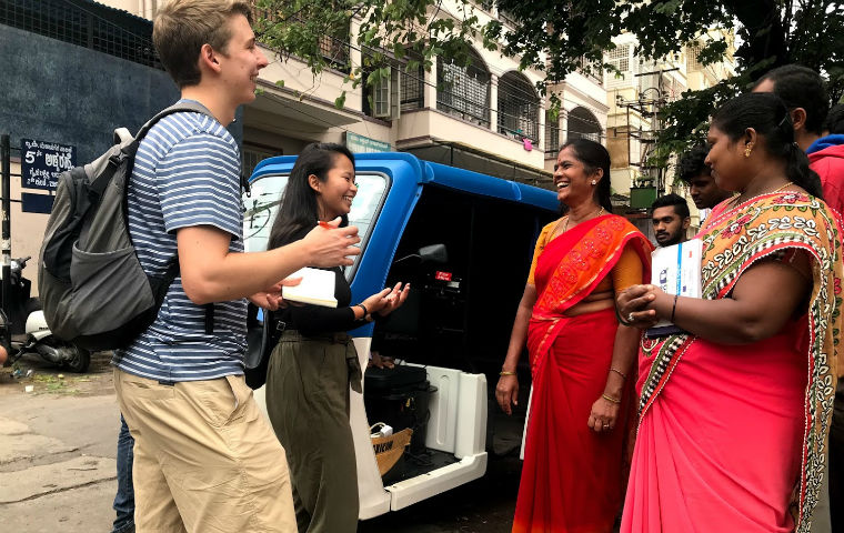 GSBF fellows smiling with women wearing red saris