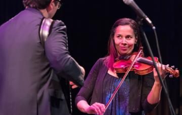 Rhiannon Giddens plays fiddle next to accordion player and musical partner Francesco Turrisi.