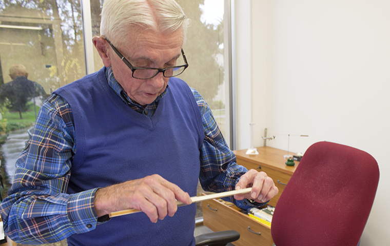 Engineering Professor Tim Healy demonstrates how to use his old slide rule, which were replaced with calculators after he arrived at Santa Clara.