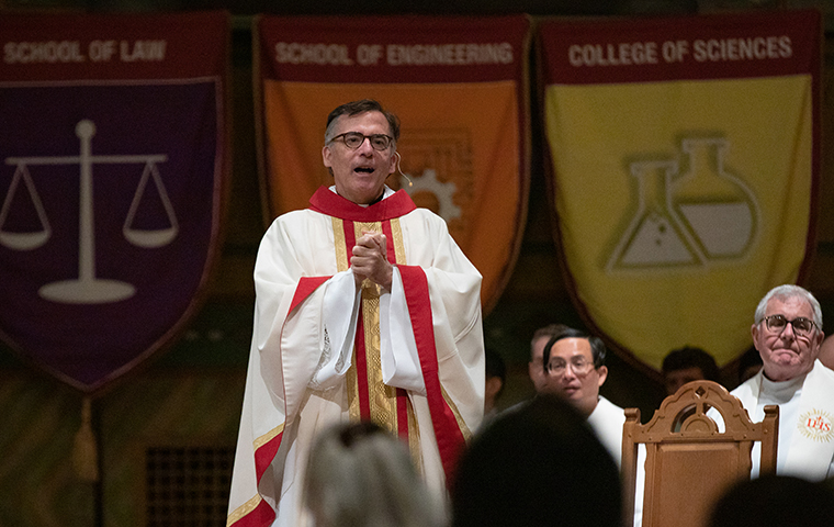 Fr. Kevin O'Brien speaks in the Mission Church with academic flags hanging in the background