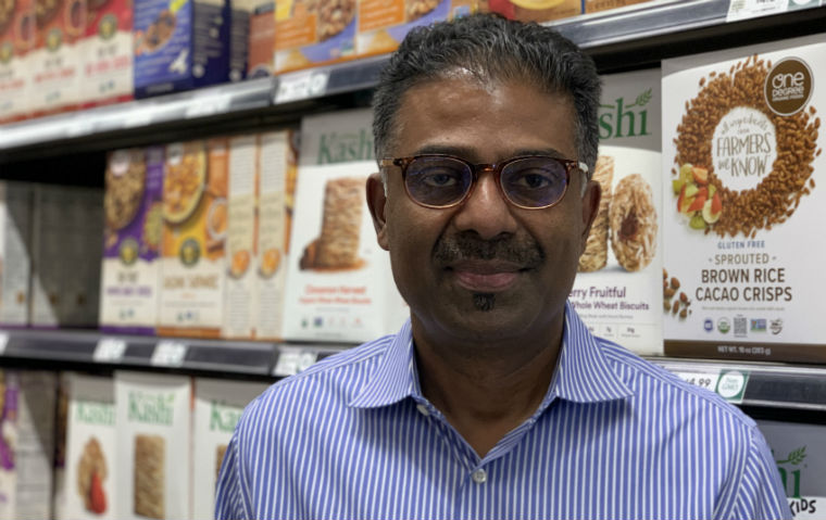 Prof. Kirthi Kalyanam poses in front of Whole Foods merchandise image link to story