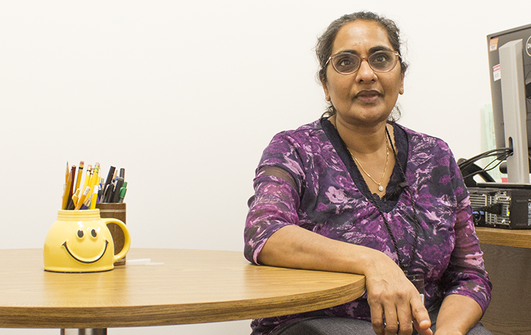Professor Shoba Krishnan sits at the small round table where she meets with students one-on-one.