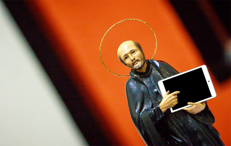 A figurine of a religious person holding an iPad image link to story