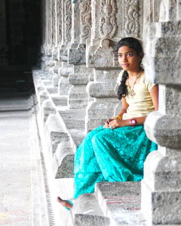 Photo of teen girl in India sitting next to temple