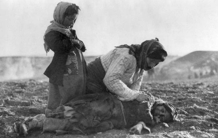 An Armenian woman and young girl check on the fallen body of another young girl. image link to story