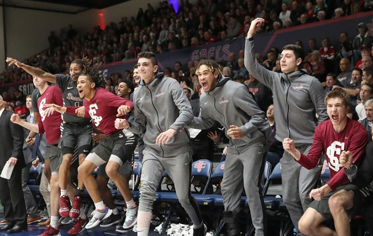 The men's basketball bench erupts in celebration against St. Mary's image link to story