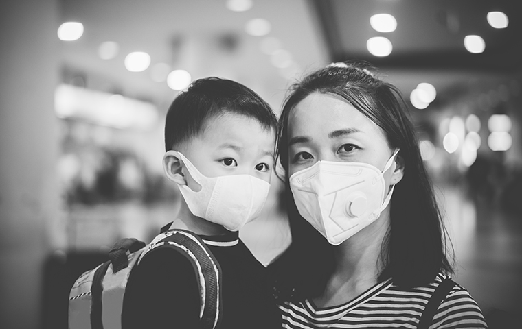 An asian mother and child wearing masks in an airport image link to article