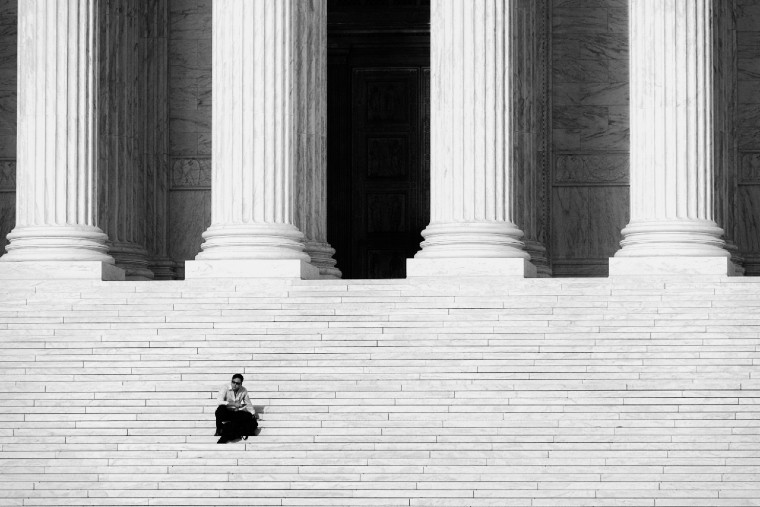 Man seated on expansive courthouse steps with columns behind him image link to story