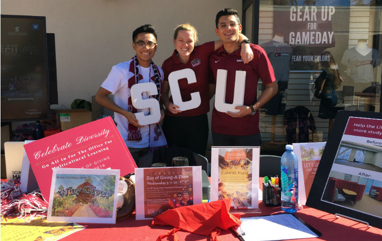 Students posing with SCU signs for Day of Giving image link to story