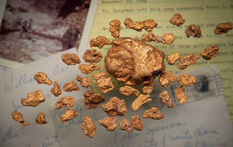 Gold Nuggets resting on top of a collage of letters, photos, and historical documents image link to story