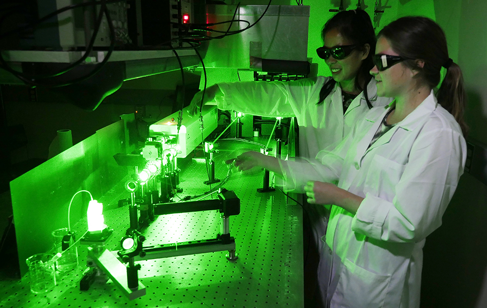 Grace Stokes using a green laser in her research
