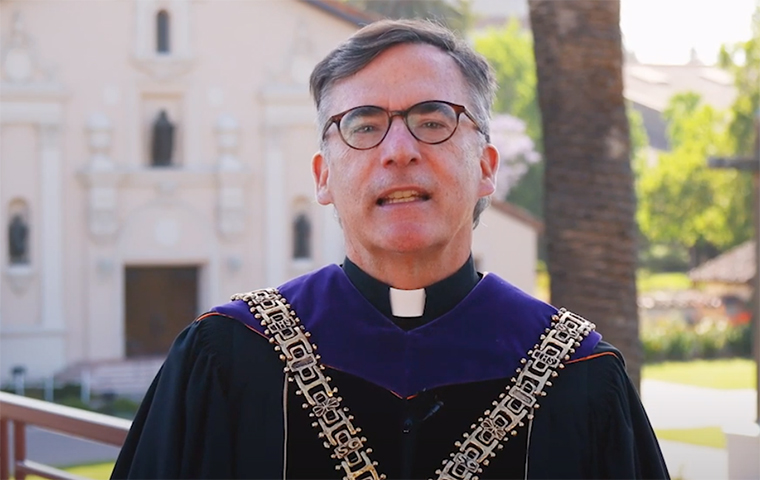 President Kevin O'Brien stands in front of the Mission Church in regalia