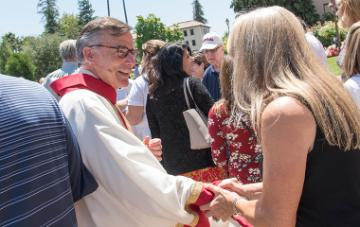 President Kevin O'Brien shaking the hand of a staff member after the Feast of St. Ignatius