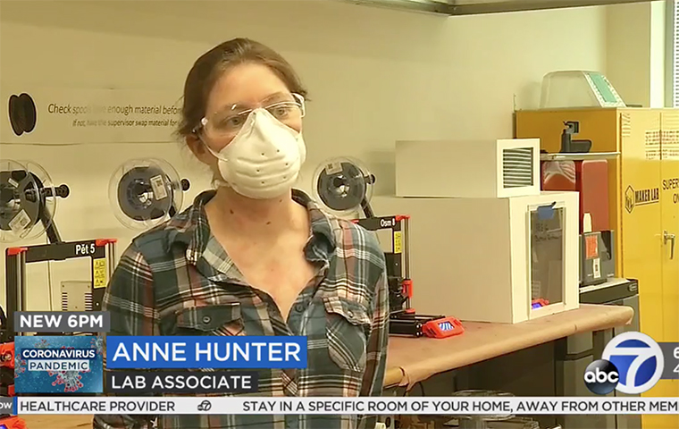 Anne Hunter speaks to camera in front of 3-D printers