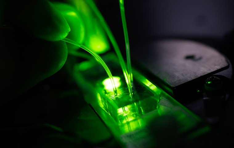A microfluidic device with green light projecting through it