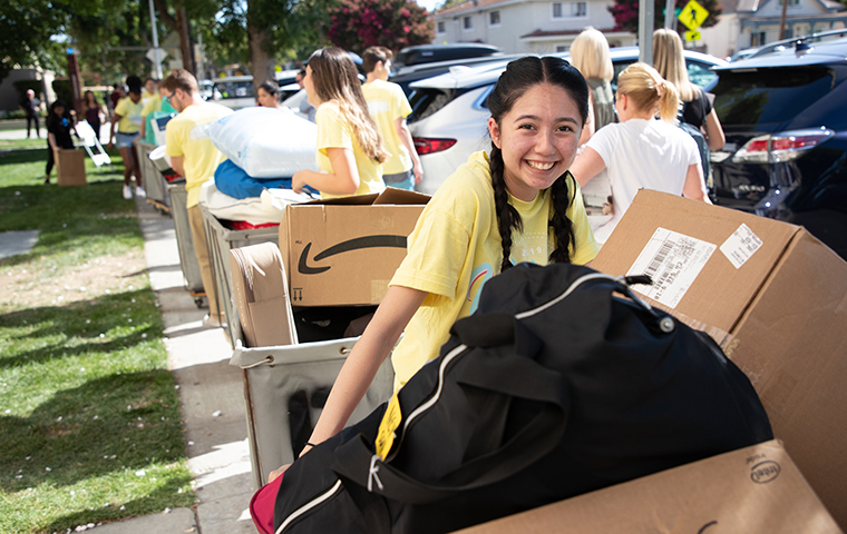 Student loads up a box for move-in at SCU image link to story