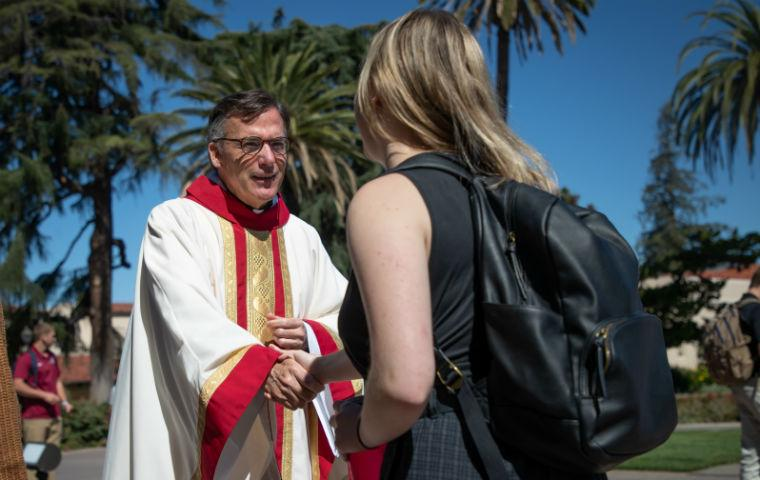 Fr. O'Brien in clerical garb shaking hand of female student, seen from behind student