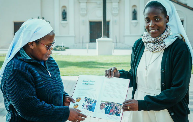 Two ACWECA Sisters holding a booklet in front of Mission Church image link to story