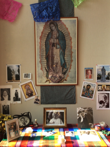 altar with pictures of loved ones and saints