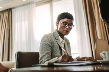 Picture of a black woman in a suit at a desk
