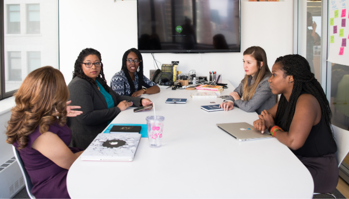 Picture of multiracial group of women sitting at a conference table
