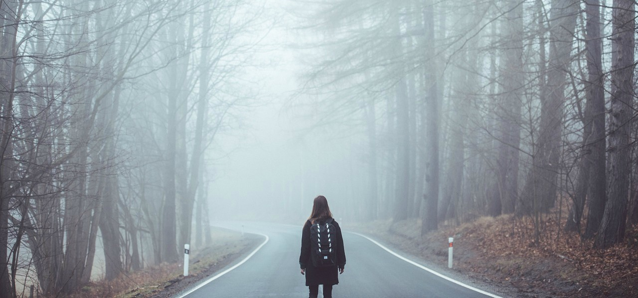 A woman walks in an empty road in a wooded area.